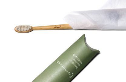 Bamboo toothbrush wrapped in tissue paper with cardboard pillow packaging