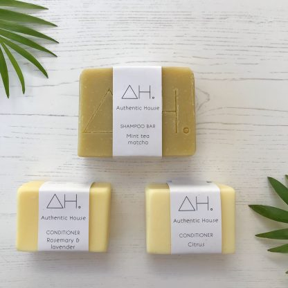 Authentic House solid shampoo and conditioner bars with white wood background and palm leave decorations. | Available at Sage Folk