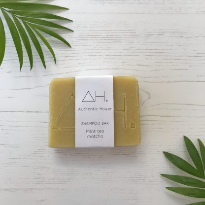 Mint and matcha solid shampoo bar with minimal cardboard packaging on white wood background with palm leaves as decoration | Available Sage Folk
