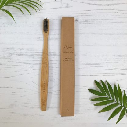 Bamboo toothbrush with soft, charcoal infused nylon bristles. Comes in cardboard packaging.. The handle is engraved with the affirmation 'breathe' | Available at Sage Folk